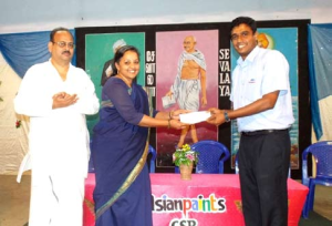 Krishnan Vaidyanathan, General Works Manager of Asian Paints handing over the cheque to Radha Srinivasan, Head Corporate Relations of Sevalaya, applauded by V. Muralidharan, Founder and Manager Trustee